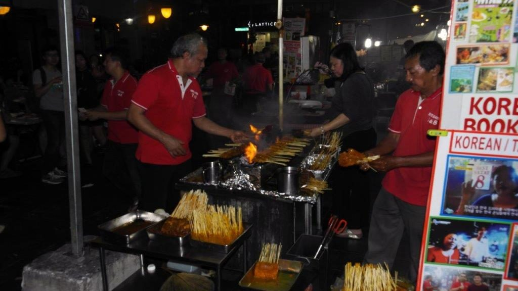 Men barbequing meat outside Lau Pa Sat,in Singapore-Dining capital of Asia