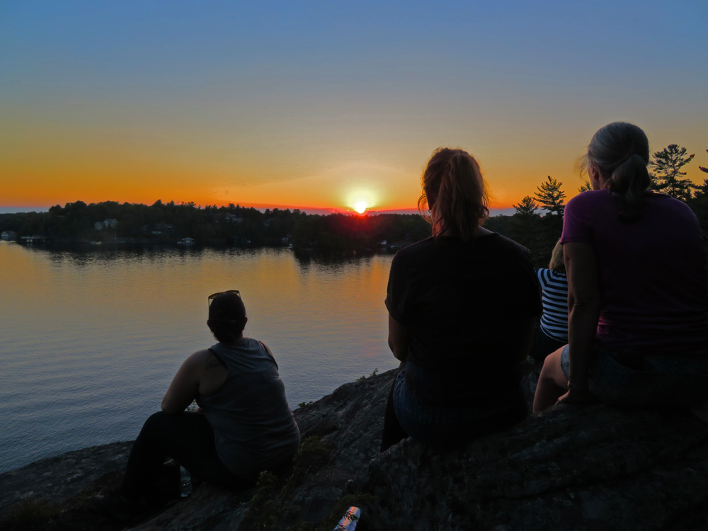 Group of women watching sunset over the lake