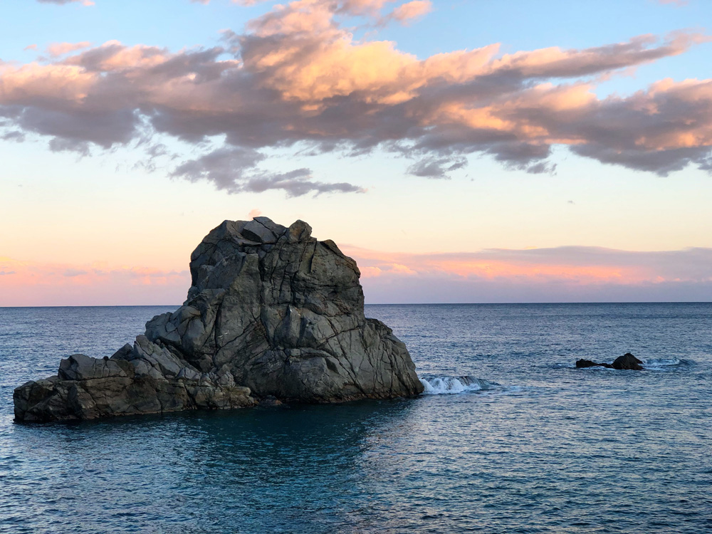 giant rock in the sea with pink sunset and clouds