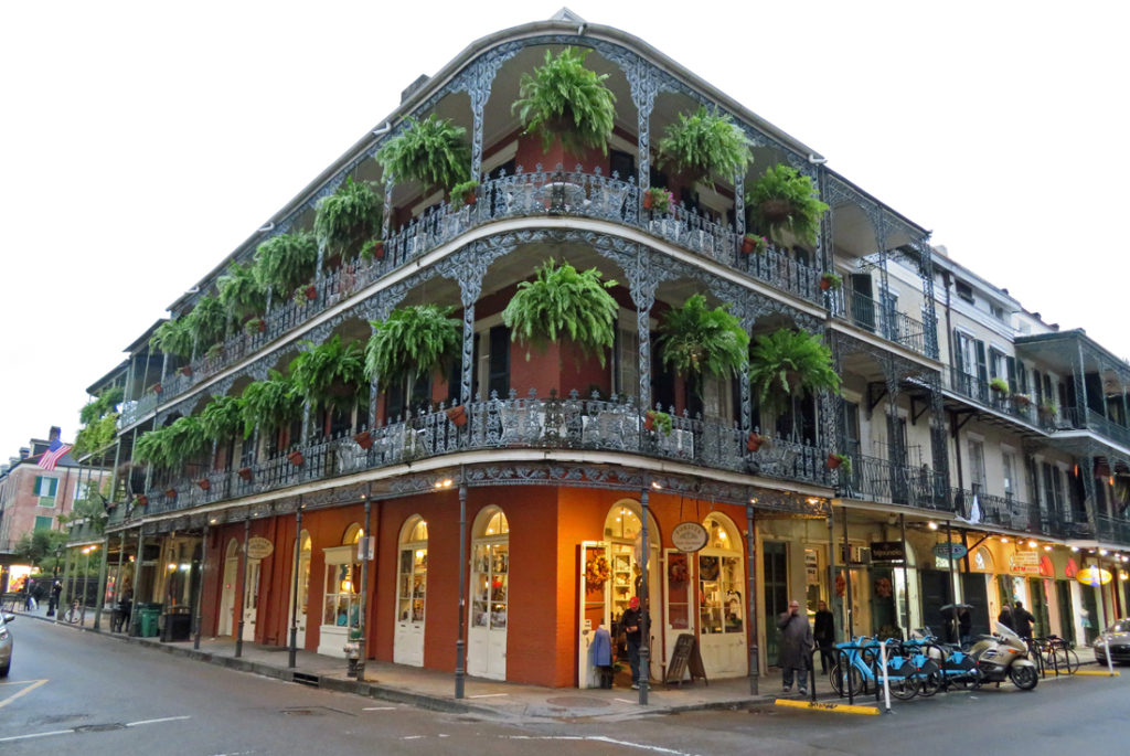 Corner view of a typical Spanish Colonial building on Bourbon St. with wrought iron balconies and ferns hanging along their length. Below are shops.
