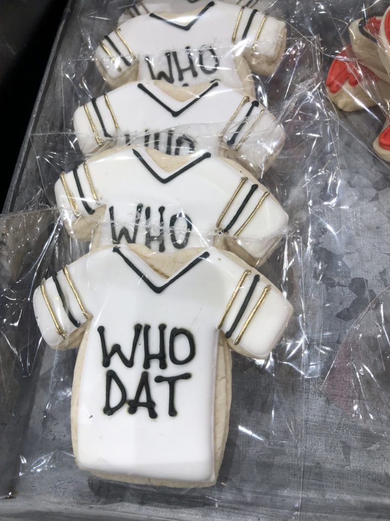 A row of t-shirt shaped cookies with Who Dat written on them,