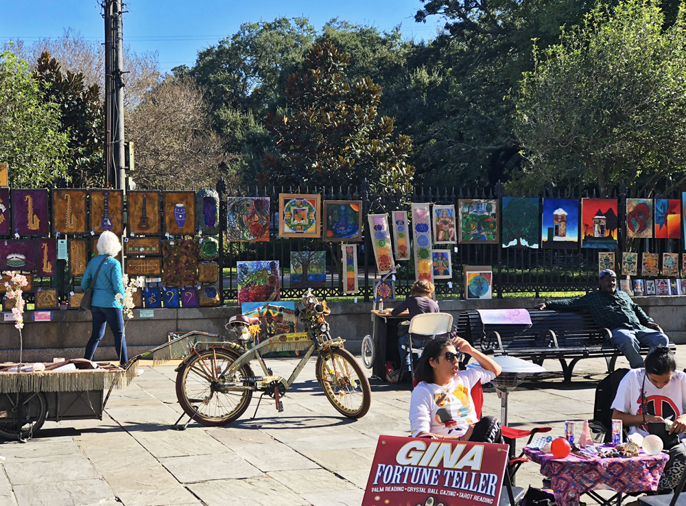 Busy scene with art hanging on the fences, people relaxing on benches and a bicycle in the middle