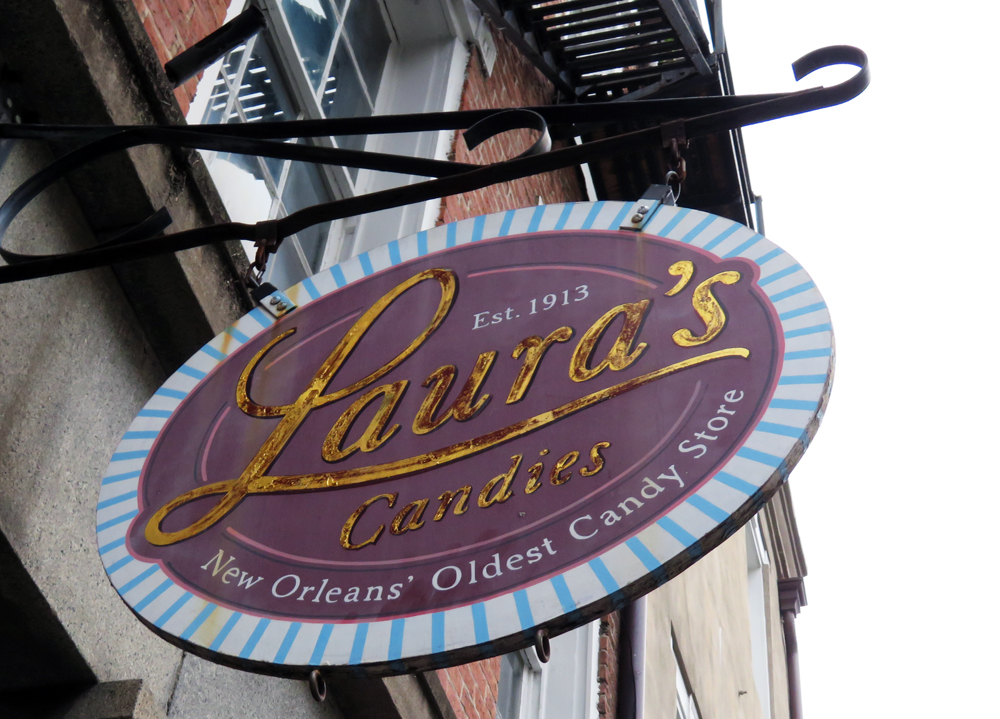 Sign hanging outside Laura's says Laura's Candies est. 1913, New Orleans Oldest Candy Store