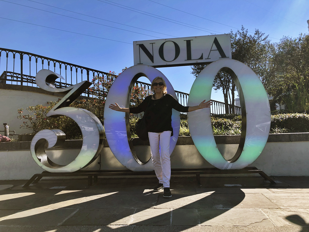 The writer standing in front of a giant 300 with NOLA on top of it.