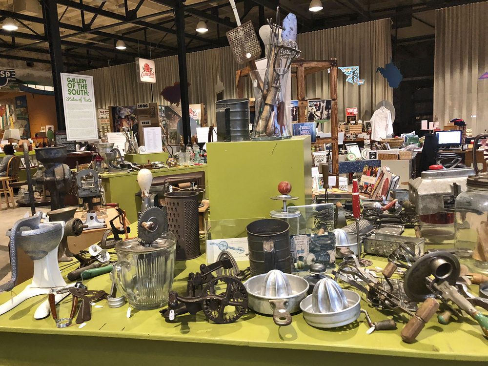 dozens of antique kitchen gadgets on a yellow table - juicer, meaL GRINDER, STRAINER, ETC.
