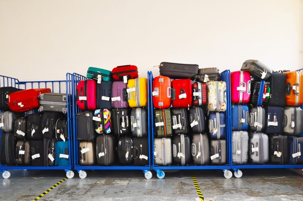 lots of suitcases on airport luggage carrier