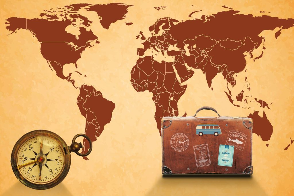 Map of the world, compass and old suitcase with labels