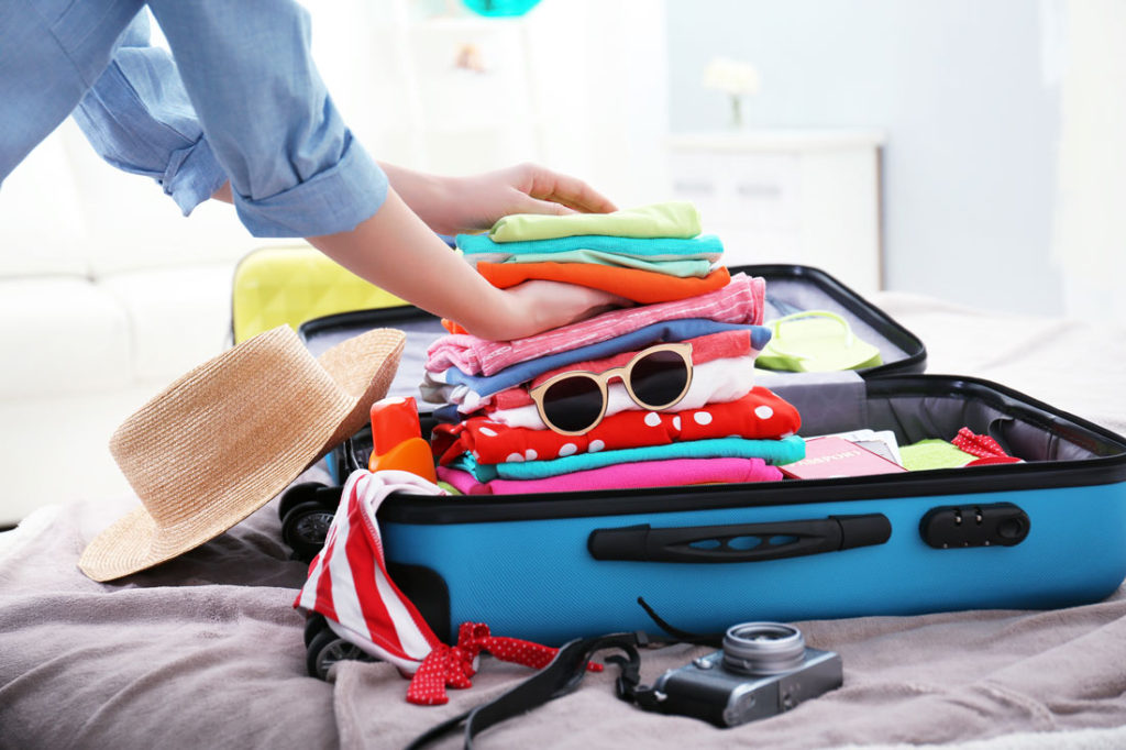 hands packing a blue suitcase with colourful clothes and sunglasses