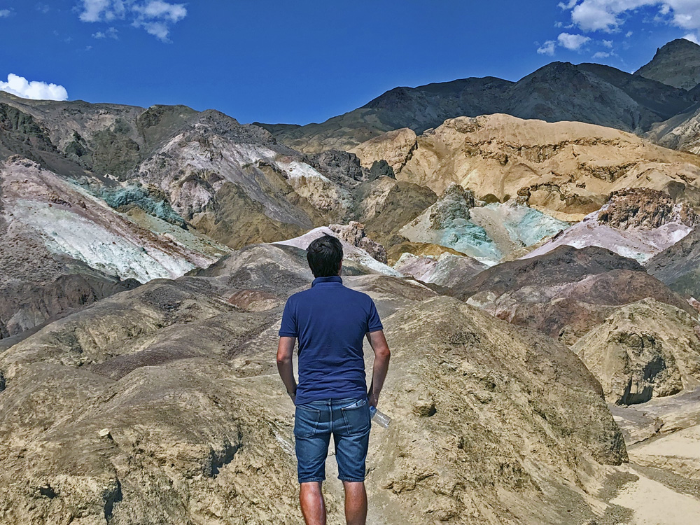 Man with his back to the camera, facing colourful stones