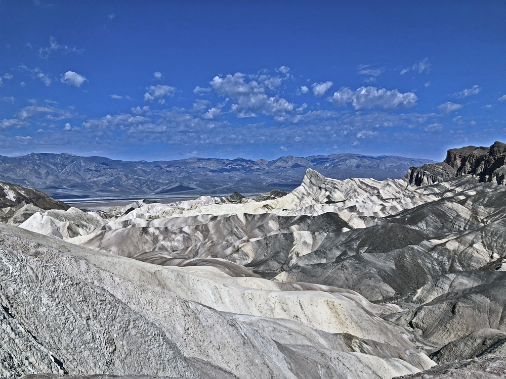 Almost white wind-sculpted stones in the foreground and blue hills in the background