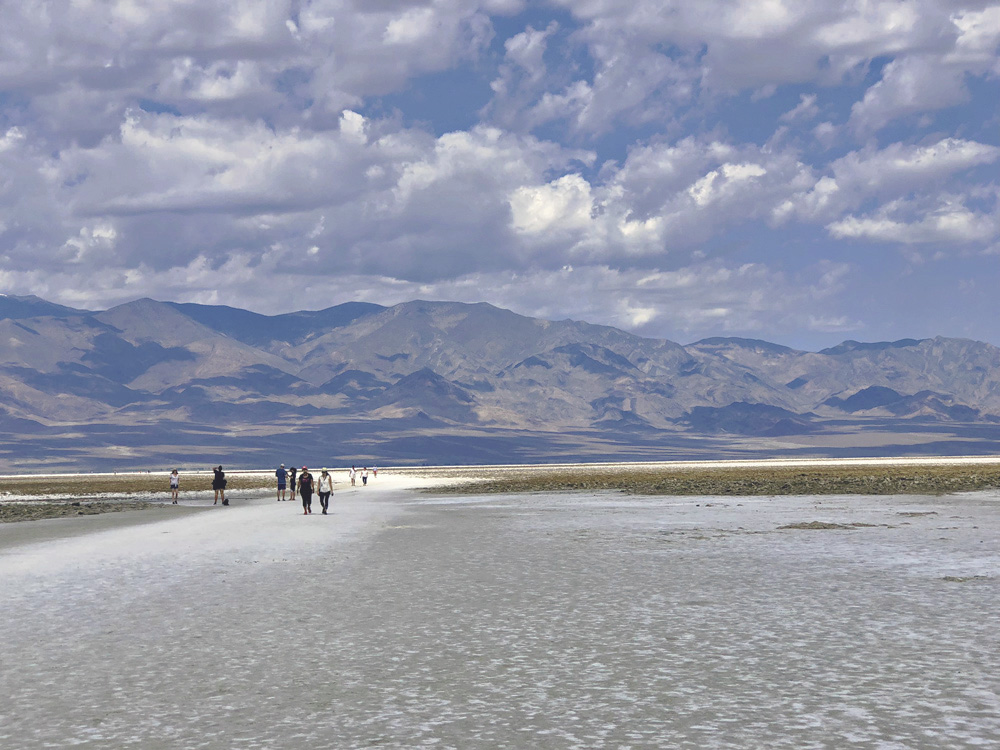people walking across salt flats at Badwater Basin; mountains in the background