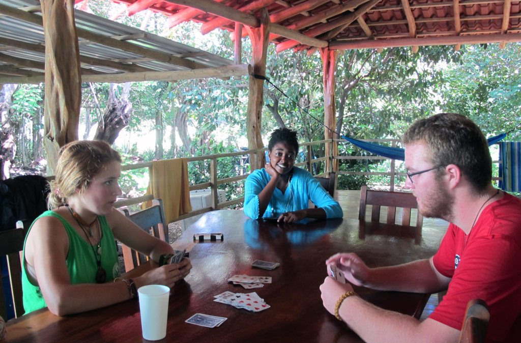 Three volunteers playing cards  at a table on a covered porch