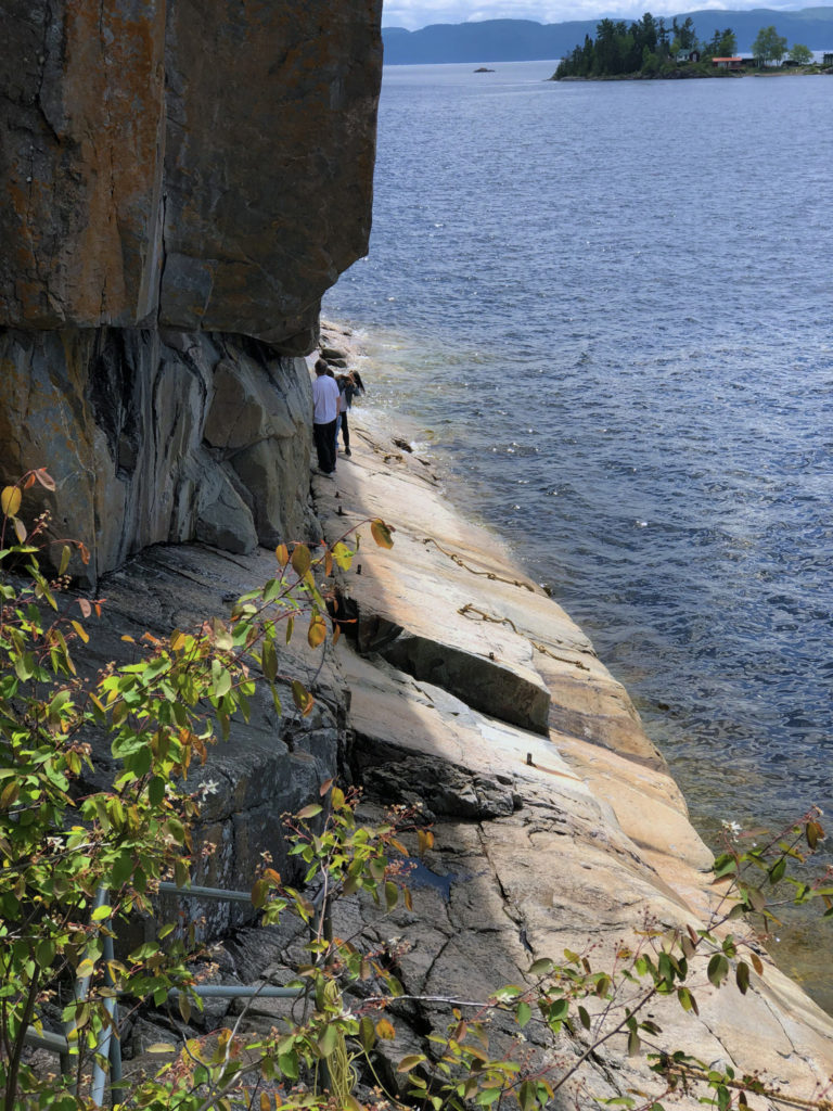 Steep rock leading down to the water with people creeping walking along Algoma Rock