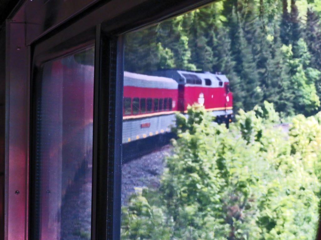 Red train seen from inside the train as it curves along the track ahead