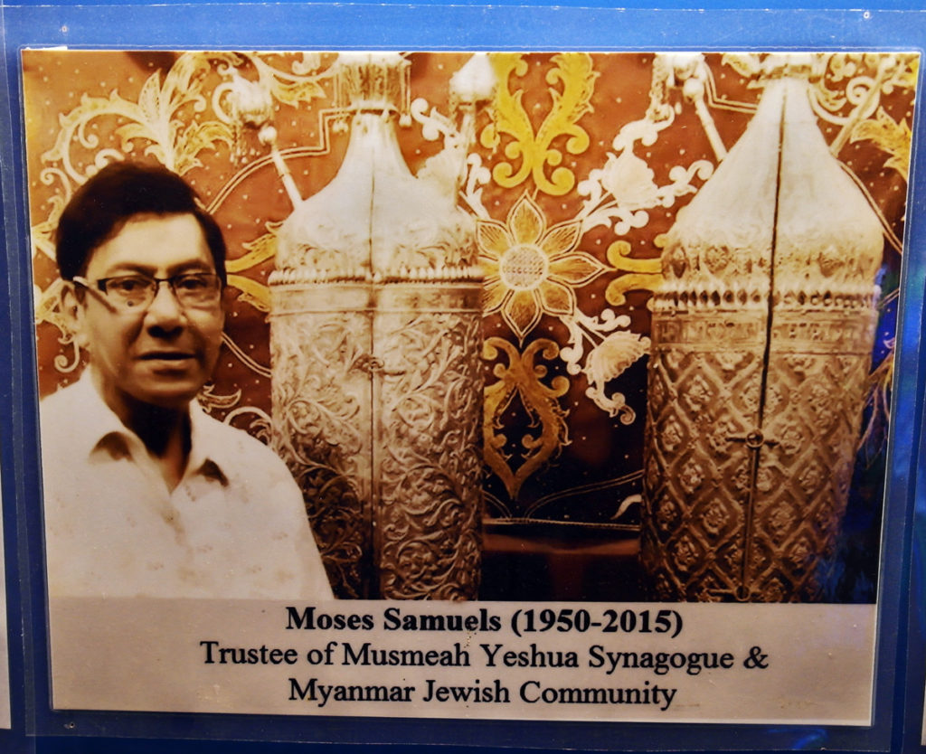 Yellowing photo of Moses Samuels standing beside the torahs.