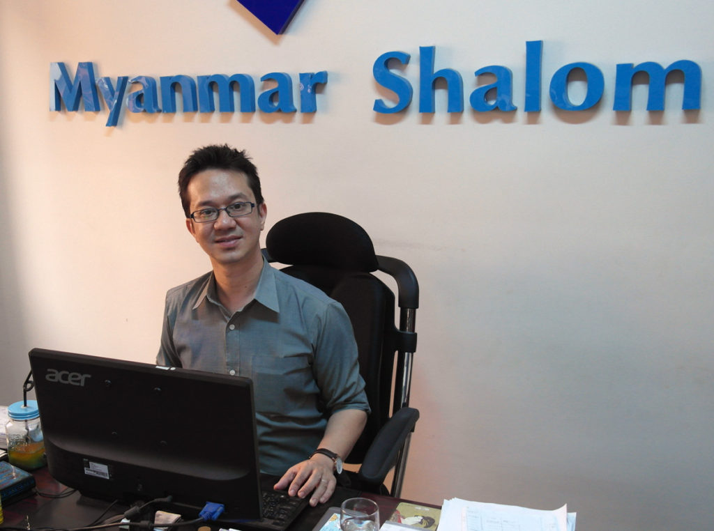 Sammy Samuels sitting at his desk with Myanmar Shalom sign in background