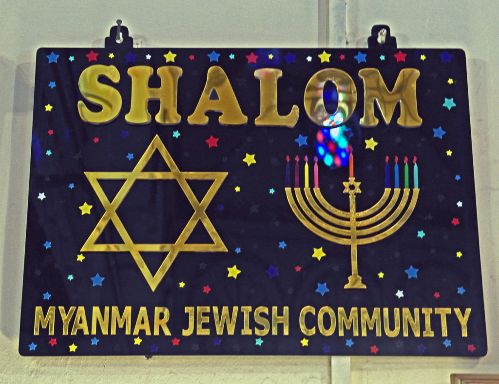 gold lettering on a blue background with many coloured tiny stars. The words read Shalom, Myanmar Jewish Community and are accompanied by a Star of David and a menorah