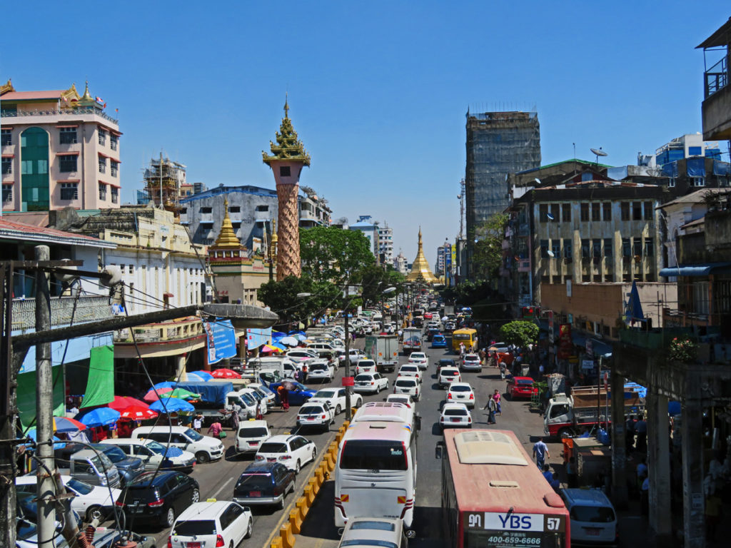 bust street with cars and buses, street markets, old buildings and temples. In the distance there's a golden stupa