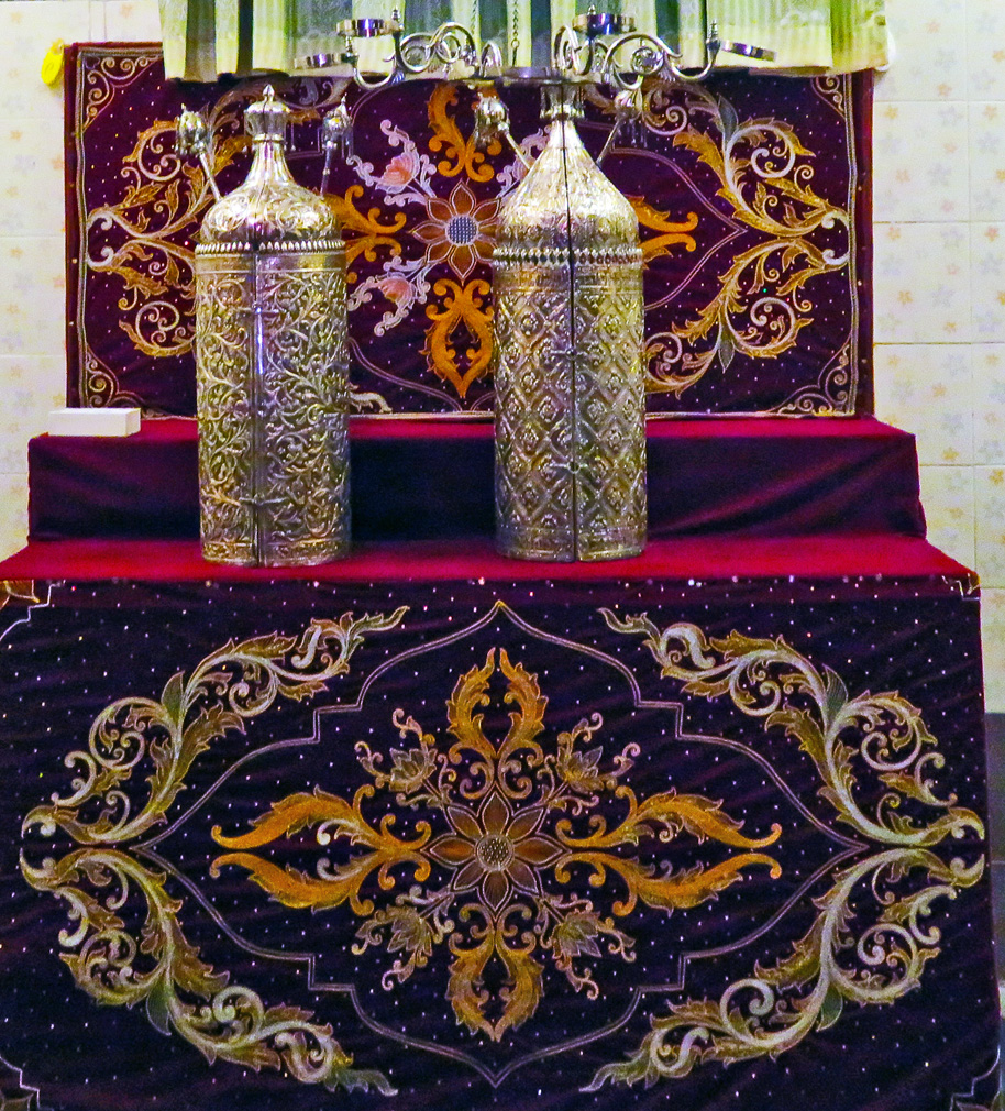 Two silver-covered torahs sit on a dias with purple velvet cloth decorated with ornate embroidery