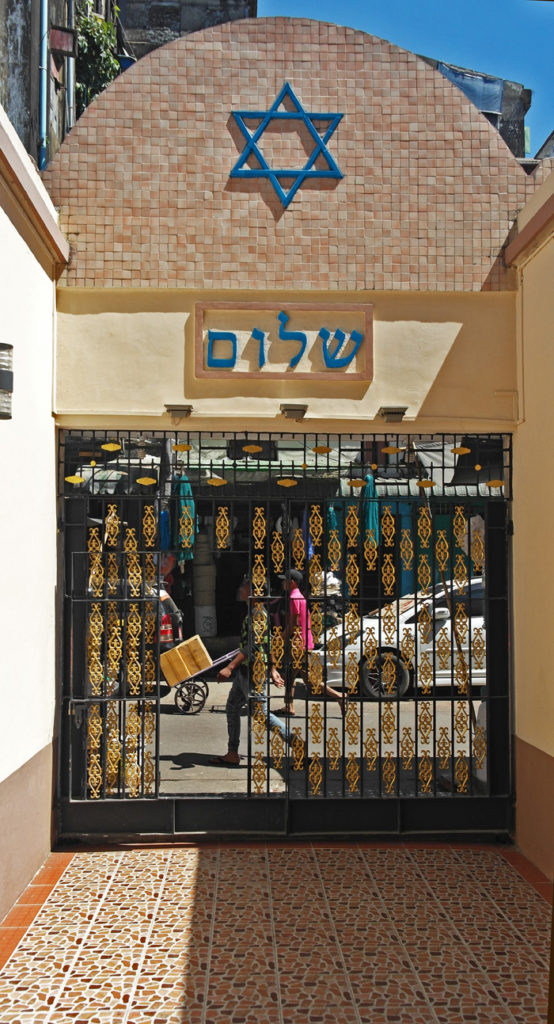 In the foreground of the tiny courtyard  is a Star of David and through the ornate gates, people rushing past
