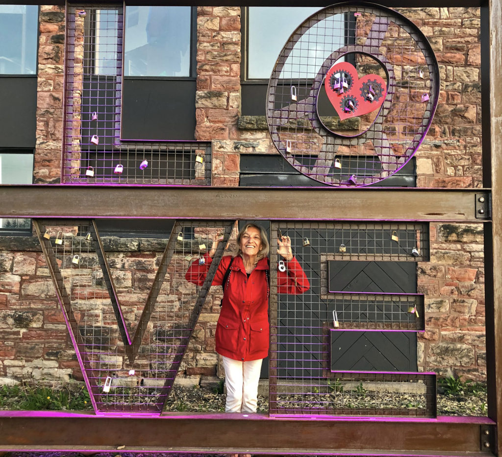 woman in red coat behind metal letters spelling LOVE with locks attached to the mesh